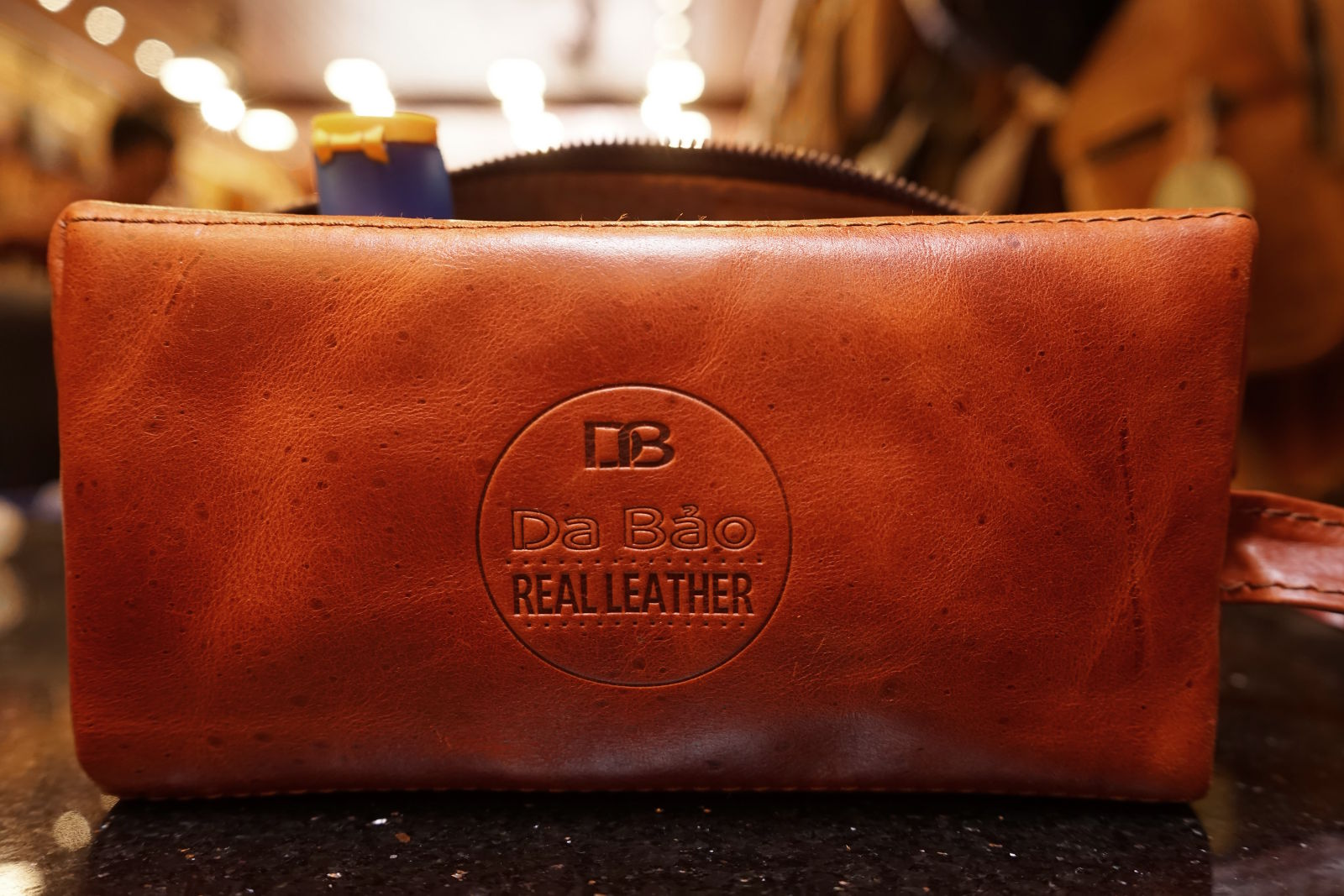 Real Leather Hoi An - Da Bao Real Leather: Front view of brown buffalo leather toiletry bag with Da Bao logo.