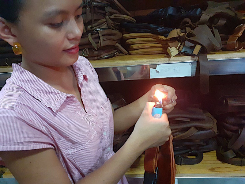 Hoi An Real Leather - Da Bao Real Leather: Ha performing the leather test on one f our leather bags