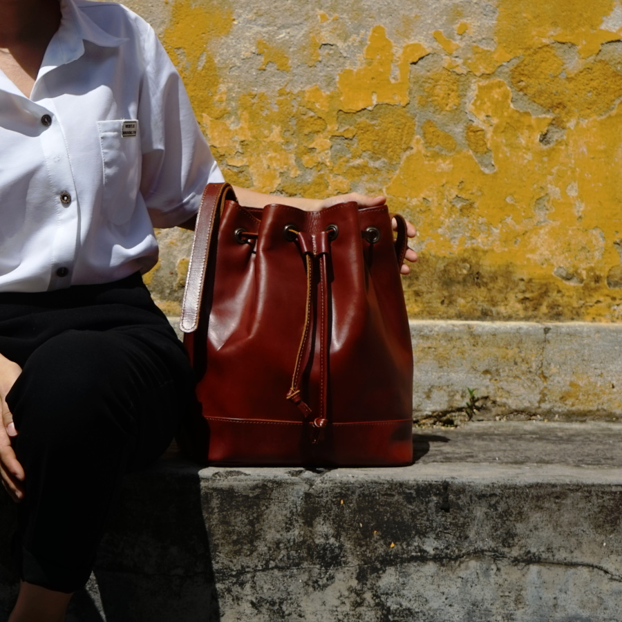 Hoi An Real Leather - Da Bao Real Leather: Brown bucket bag in front of yellow wall in Hoi An Old Town